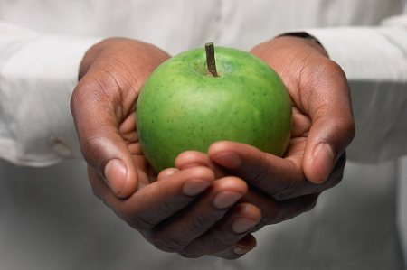 Man in white shirt holding green apple uid 1341813